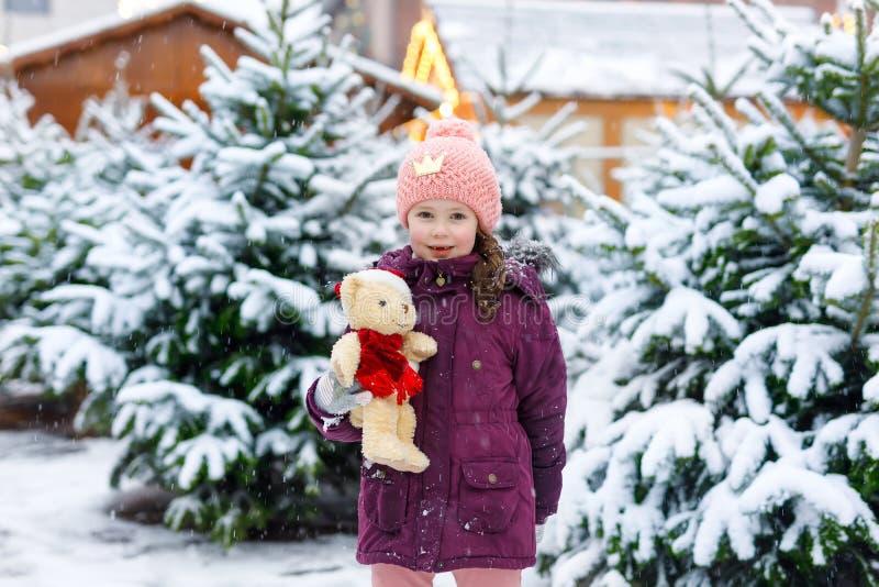 在圣诞树市场上的逗人喜爱的矮小的微笑的孩子女孩 选择在xmas的冬天衣裳和玩具的愉快的孩子xmas树 库存图片