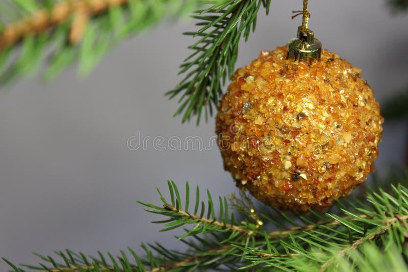 在圣诞树的琥珀色的球在白色背景 在光的宝石琥珀色的淡光 橙色光 圣诞节装饰生态学木 免版税库存图片