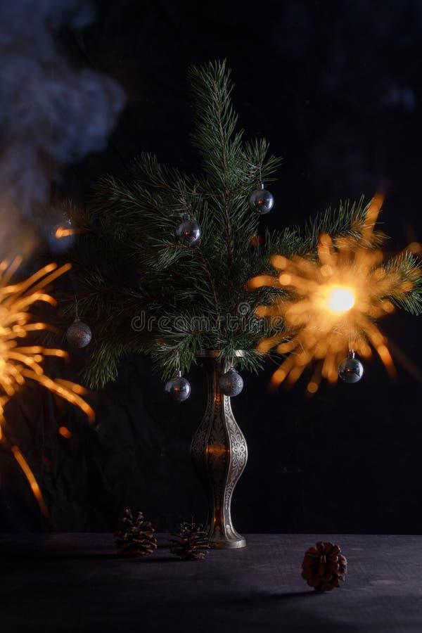 在圣诞树的背景的孟加拉火,装饰用圣诞节玩具 新年的大气 免版税库存照片