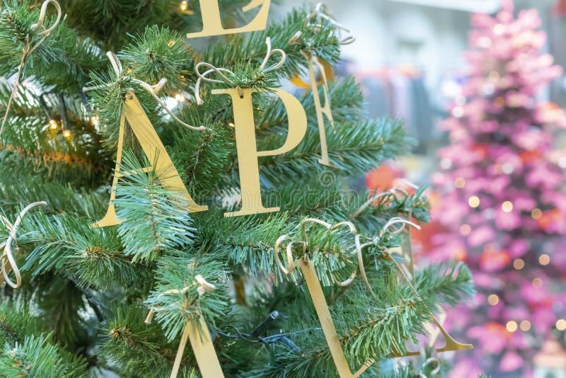 在圣诞树的装饰以金信件的形式 库存图片