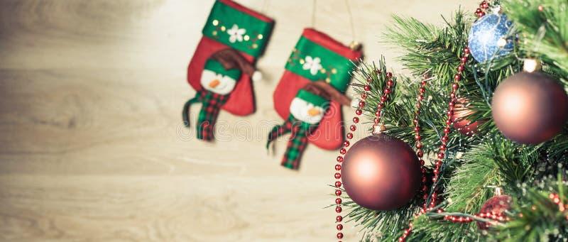 在圣诞树的装饰的红色球与在背景的袜子 图库摄影