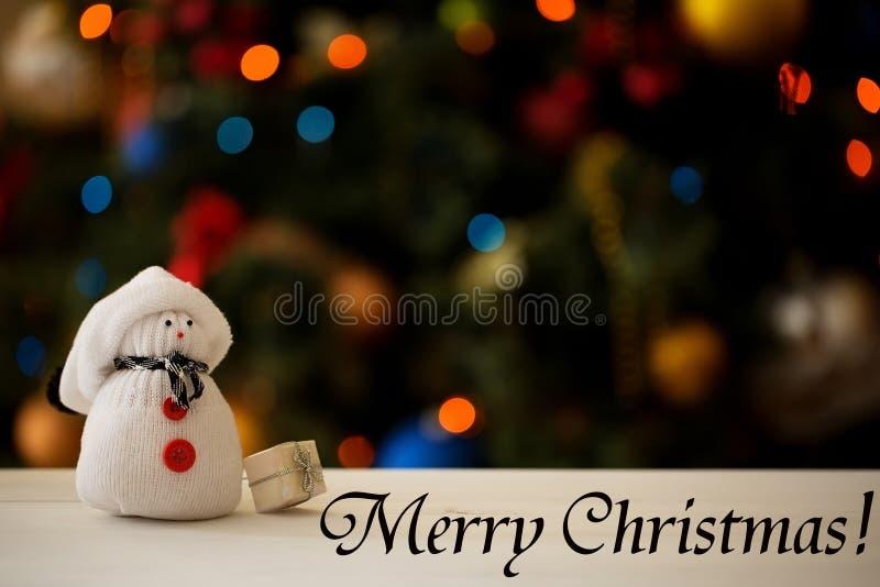 在圣诞树背景的雪人与题字 免版税库存图片