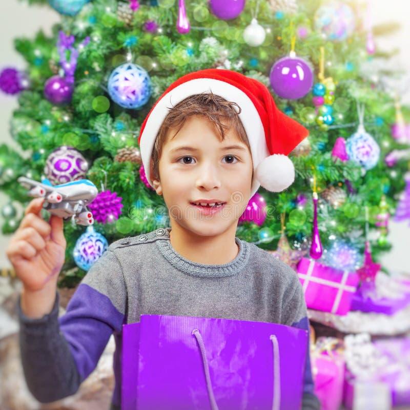 在圣诞树附近的愉快的男孩 免版税库存照片