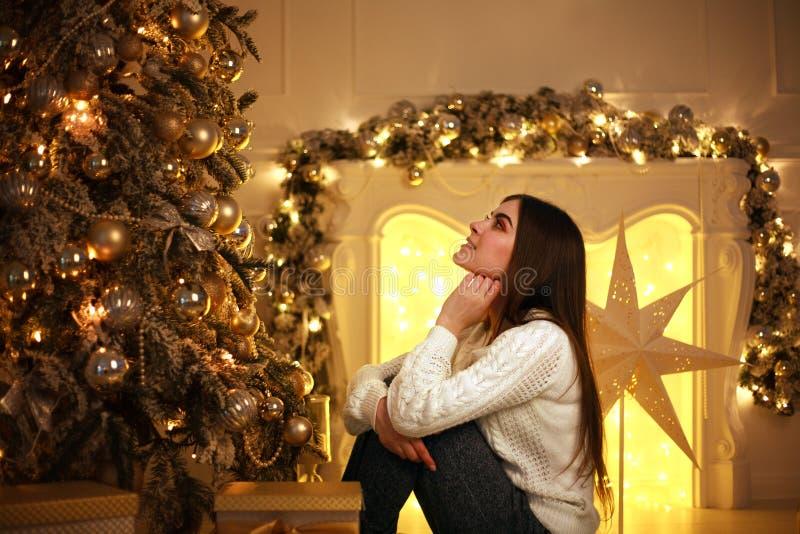 在圣诞树附近的梦想的妇女与光装饰 免版税库存照片