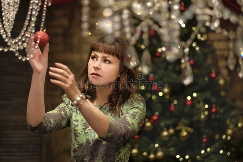 在圣诞树附近的美丽的妇女 库存图片