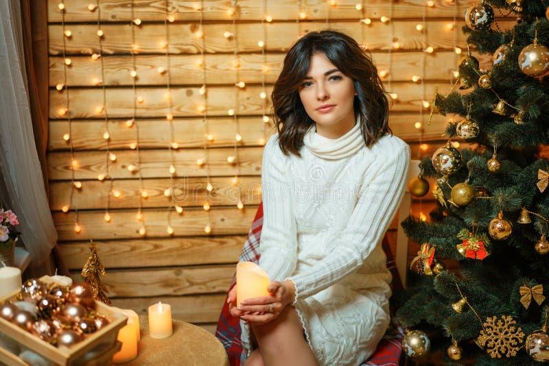 在圣诞树附近的美丽的年轻女人在一个白色毛线衣、舒适等待的新年和圣诞节假日 免版税图库摄影