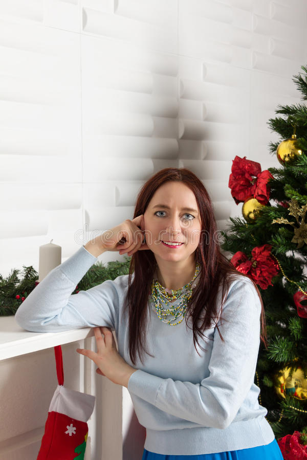 在圣诞树附近的美丽的愉快的妇女 免版税图库摄影