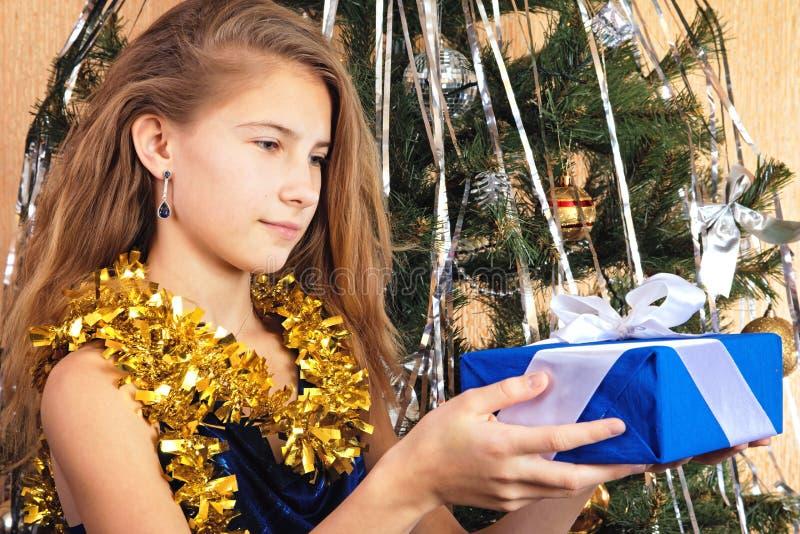 在圣诞树附近的美丽的青少年的女孩愉快地看礼物 库存照片