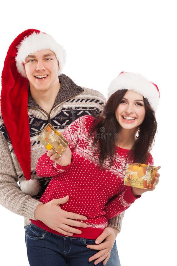 在圣诞树附近的年轻愉快的夫妇。 库存照片