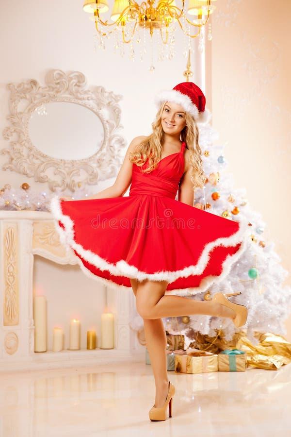 在圣诞树附近的年轻美丽的微笑的圣诞老人妇女 Gir 库存图片