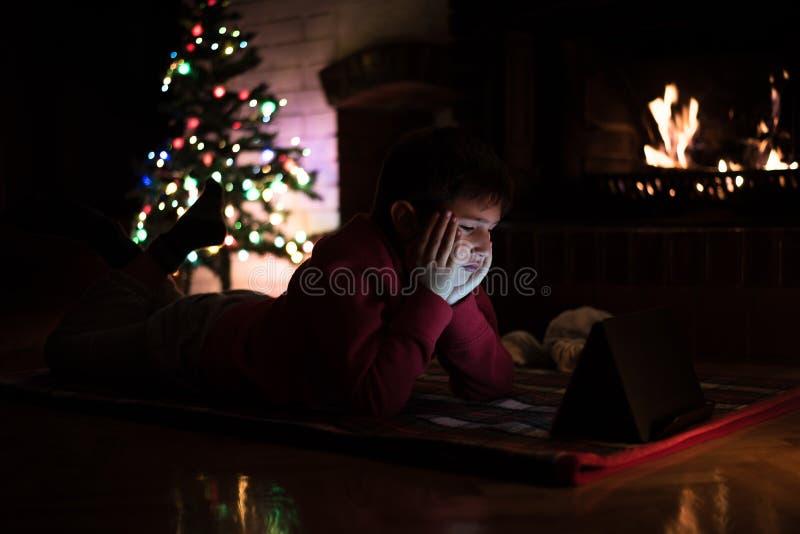 在圣诞树a旁边的男孩观看的片剂 免版税库存照片