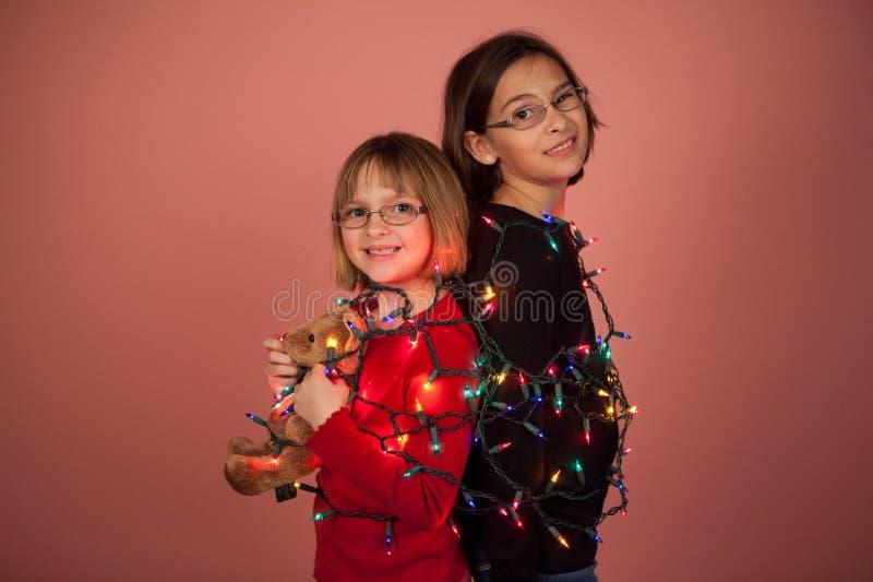 在圣诞灯包裹的孩子为假日 免版税库存图片