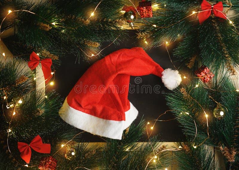 在圣诞灯围拢的黑板的圣诞老人帽子,装饰品 免版税库存图片