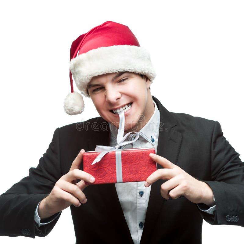 在圣诞老人帽子尖酸的礼物的商人 免版税图库摄影