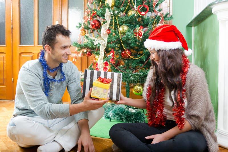 在圣诞老人帽子的夫妇有圣诞节和新年礼物的 免版税库存照片
