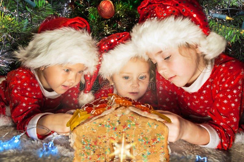 在圣诞老人帽子的孩子有圣诞节 免版税库存图片