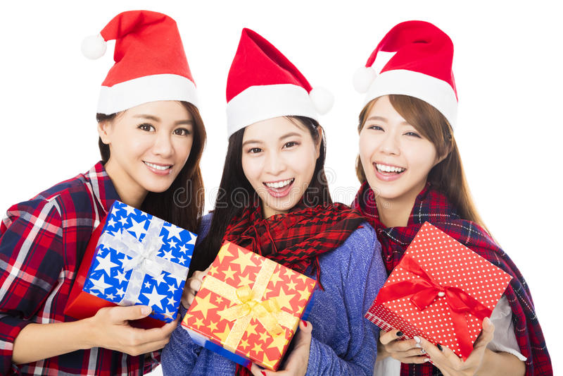 在圣诞老人帽子的少妇小组有礼物盒的 免版税图库摄影