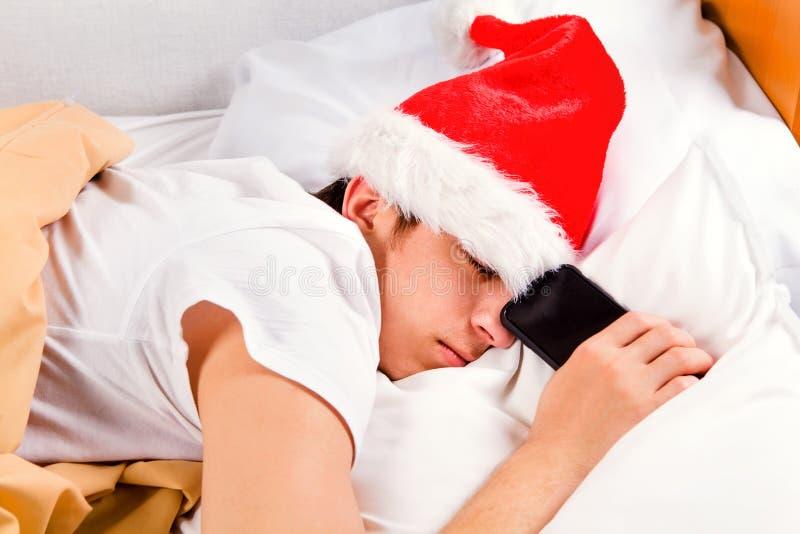 在圣诞老人帽子的年轻人睡眠 免版税库存照片
