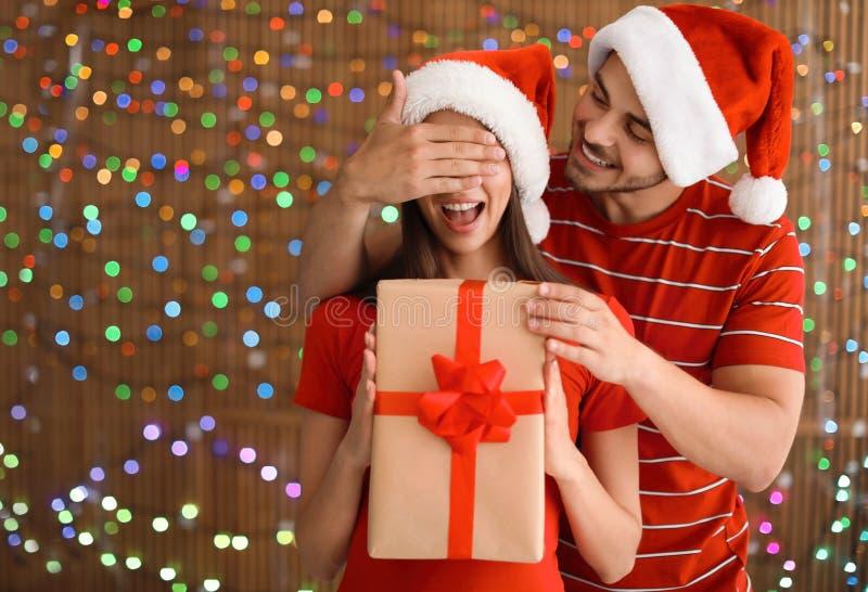在圣诞老人帽子的年轻夫妇有圣诞节礼物的 免版税库存照片