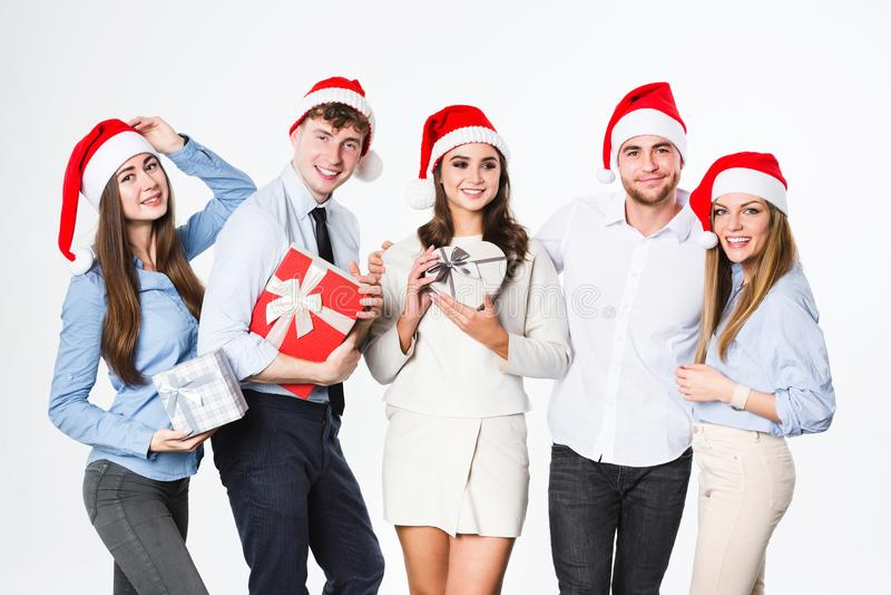 在圣诞老人帽子的愉快的人小组有在白色背景隔绝的礼物的 免版税库存图片