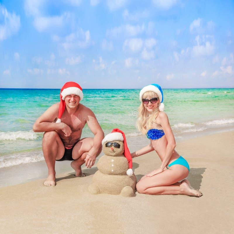 在圣诞老人帽子的桑迪雪人和在海滩的年轻愉快的夫妇 库存照片
