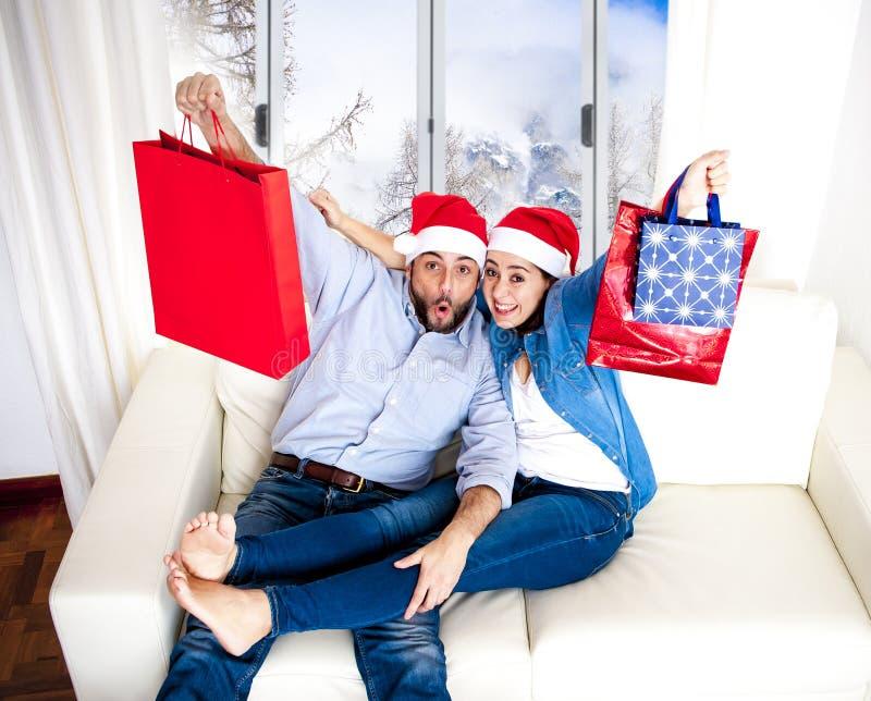 在圣诞老人帽子的年轻愉快的夫妇在拿着与礼物的圣诞节购物袋 免版税库存图片
