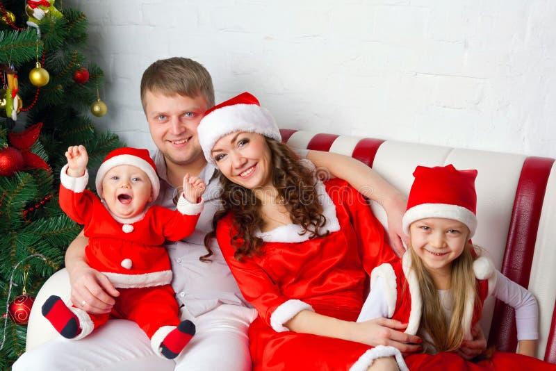 在圣诞老人服装的愉快的家庭 免版税图库摄影