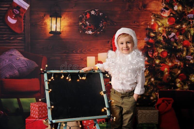 在圣诞老人的圣诞节打扮的男孩 图库摄影