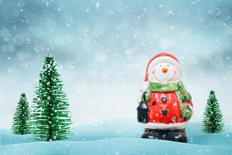 在圣诞老人项目衣裳的逗人喜爱的雪人 此外圣诞树 免版税库存图片
