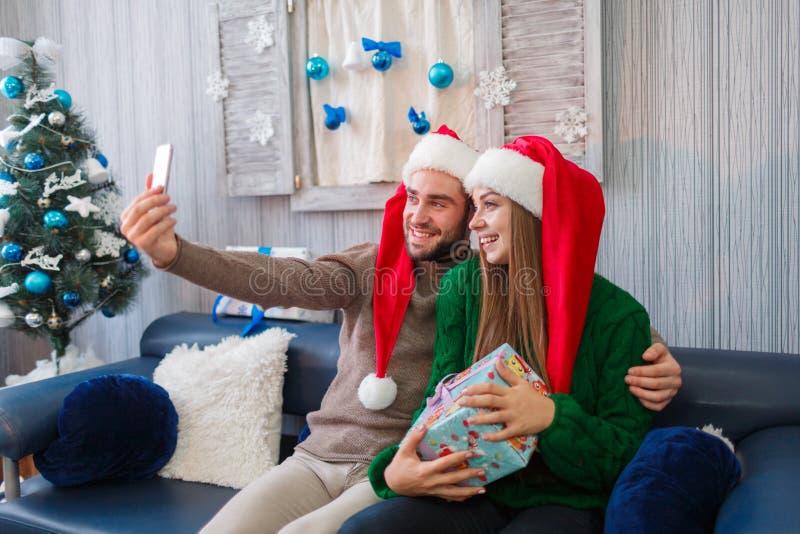 在圣诞老人` s帽子的一对愉快的夫妇在手机做selfie,拿着礼物盒 户内 库存照片
