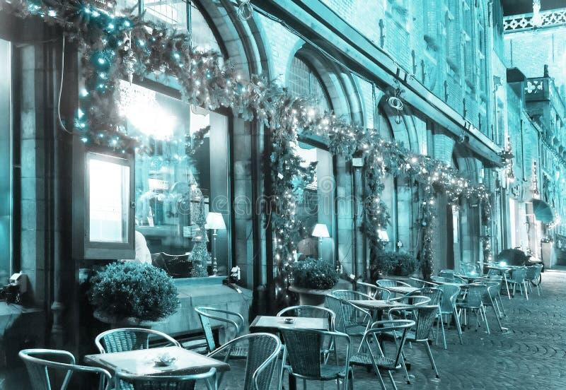 在圣诞节假日装饰的咖啡馆 在前景是桌和椅子站立在街道上的客户的 免版税库存照片