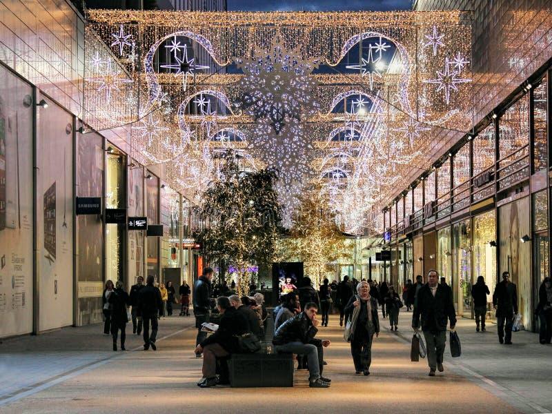 在圣诞节前的人夜间购物 免版税库存照片