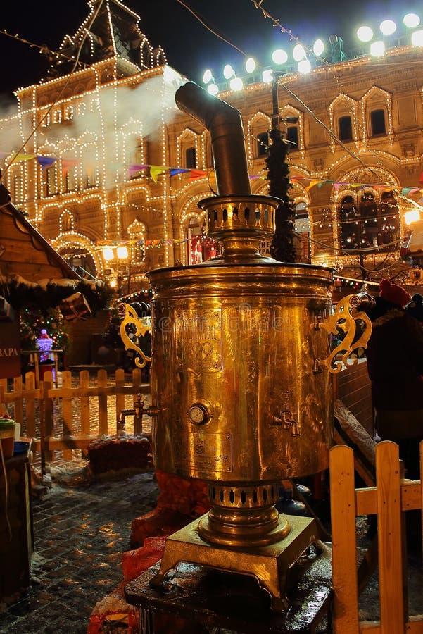 在圣诞节和新年` s的巨大的俄国式茶炊公平在装饰的主要普遍商店的背景分泌树液 免版税库存照片