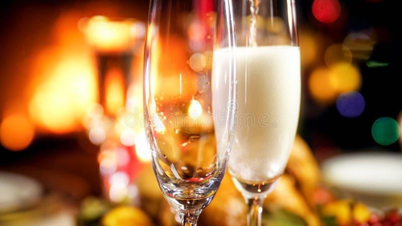 在圣诞节家庭晚餐被填装的两块香槟玻璃的特写镜头图象 库存图片
