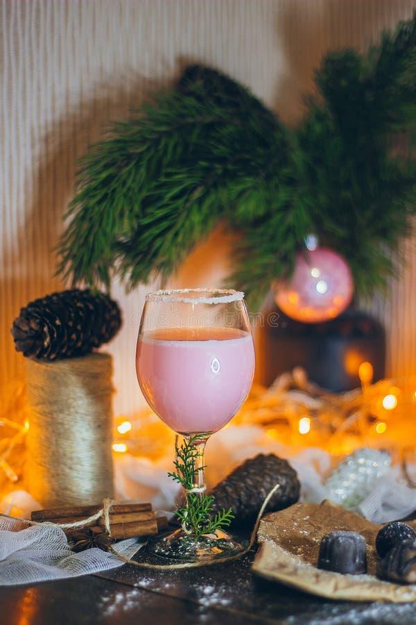 在圣诞节心情的一个美好的静物画场面与一杯桃红色饮料和甜点在圣诞灯和毛皮t 免版税库存图片