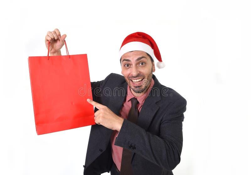 在圣诞节拿着和指向在12月和新年销售的圣诞老人帽子的年轻可爱的商人红色购物袋 图库摄影