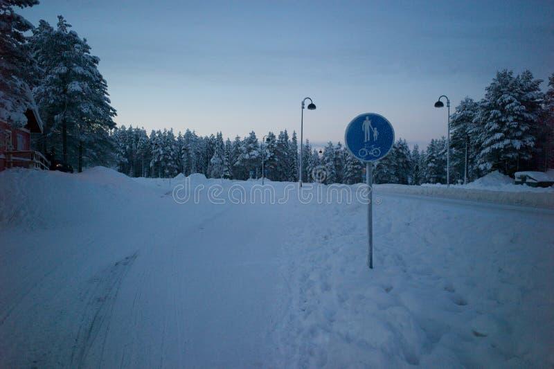 在圣诞节期间,步行者和自行车车道签到莱维滑雪镇,芬兰 图库摄影