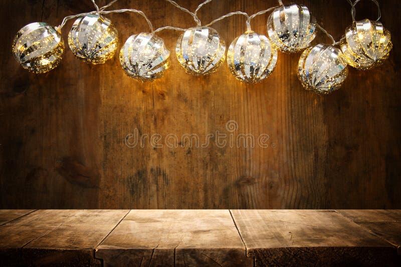 在圣诞节温暖的金诗歌选光前面的空的桌在木背景 免版税库存照片