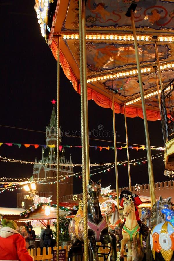 在圣诞节的五颜六色的转盘马公平在红场反对克里姆林宫的背景在晚上 库存图片