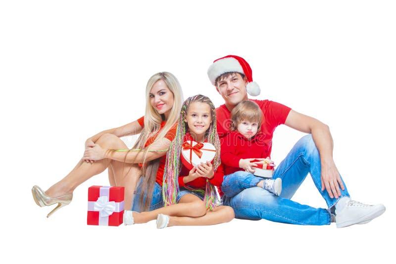 在圣诞节的系列 在微笑圣诞老人的帽子的快乐的家庭看照相机和,当隔绝在白色时 画象 库存照片