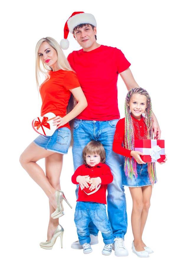 在圣诞节的系列 在微笑圣诞老人的帽子的快乐的家庭看照相机和,当隔绝在白色时 画象 免版税库存照片