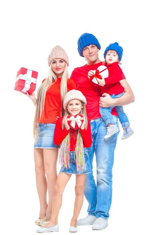 在圣诞节的系列 在微笑的帽子的快乐的家庭看照相机和,当隔绝在白色时 手中的礼物盒 库存照片