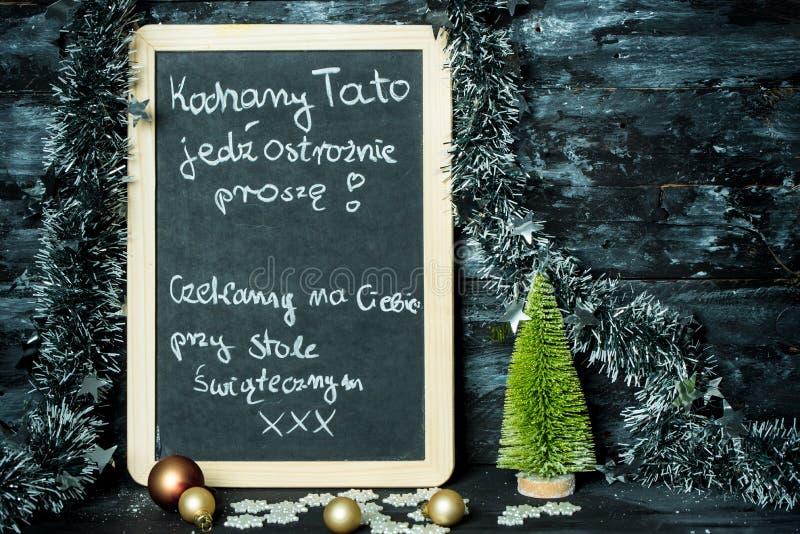 在圣诞节背景有一则消息的一个黑板从生的孩子:驾驶小心,我们等待您 库存图片