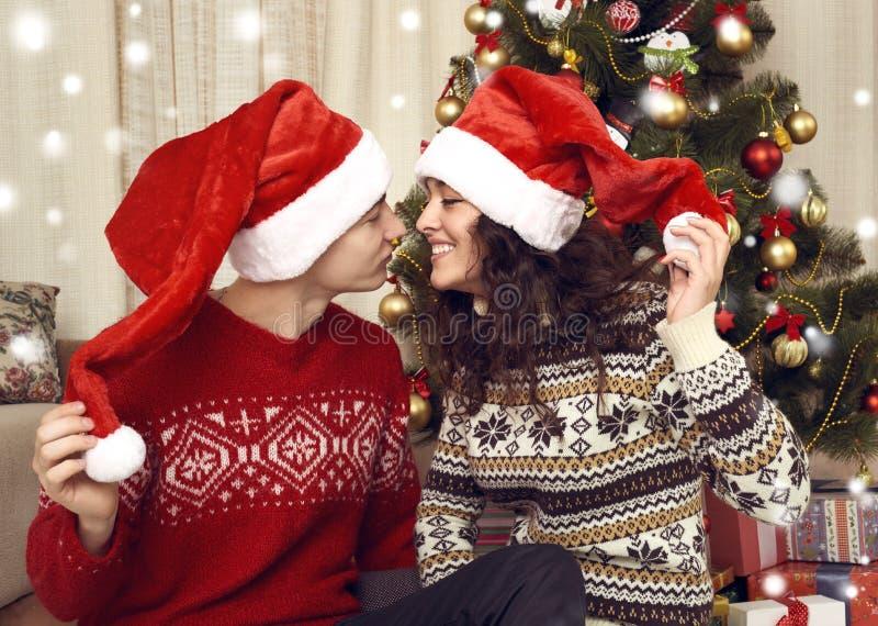 在圣诞节装饰的愉快的夫妇亲吻在家 除夕, ornated杉树 寒假和爱概念 免版税图库摄影