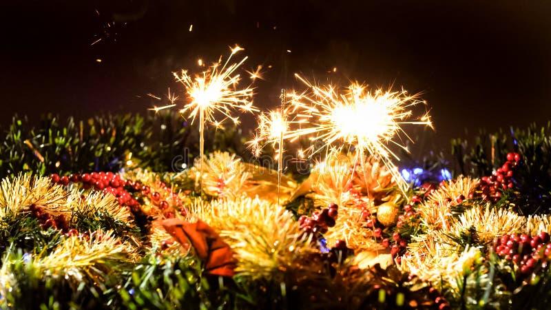 在圣诞节装饰的背景的燃烧的孟加拉火与诗歌选的 免版税库存照片