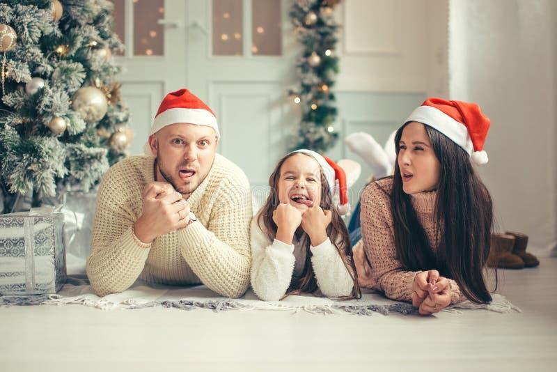 在圣诞节说谎在床上的圣诞老人帽子的家庭 获得母亲的父亲和的婴孩乐趣 免版税库存照片