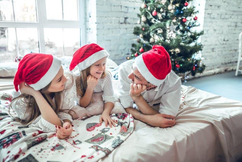 在圣诞节说谎在床上的圣诞老人帽子的家庭 免版税库存图片