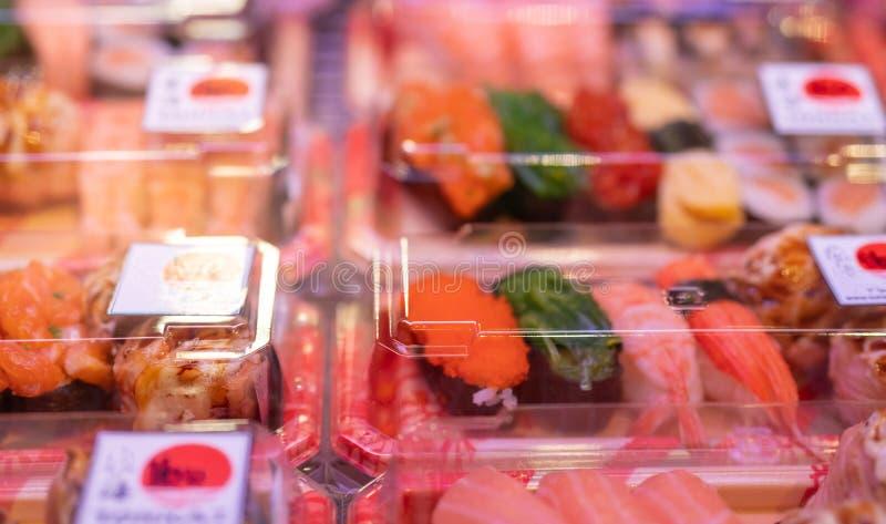 在在架子的塑料盒显示设置的寿司的选择聚焦在超级市场 日本料理为拿走 寿司交付事务 免版税库存图片