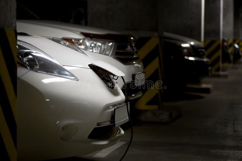 在地下停车处的白色电车 燃料在背景的汽油汽车 被连接的电源插头 未来汽车业 客栈 免版税库存图片