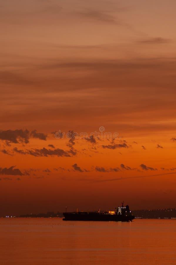 在地中海海岸的货箱船在日落 免版税库存照片